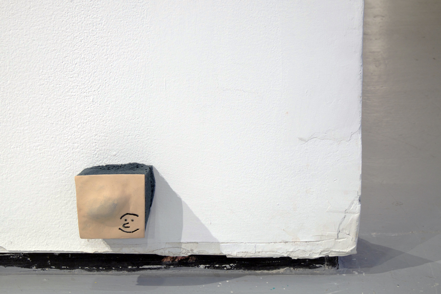 A ceramic sculpture of a square-shaped excision of an ankle. A smiley face is etched into the ankle like a tattoo. The excision is installed on the wall very close to the floor. It protrudes outward from the wall by a square piece of black foam.