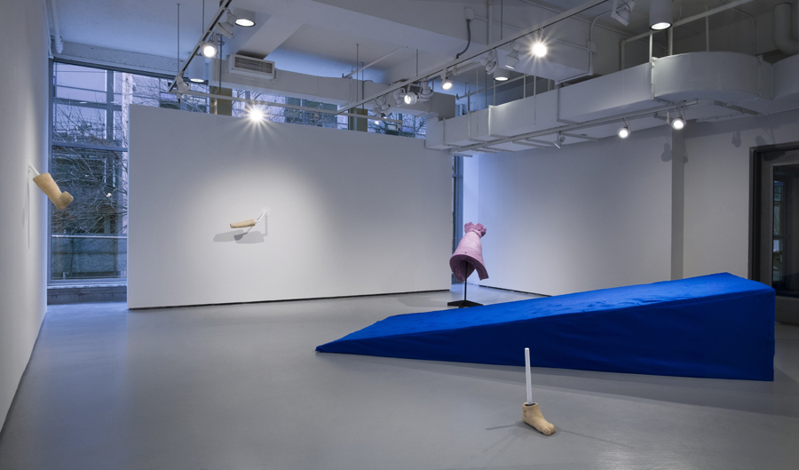 Installation view of a pristine whitewall gallery space. A large cobalt blue wedge made of fabric and foam in the middle of the gallery. Sculptures of body parts are installed sparsely on the walls and placed on the floor.