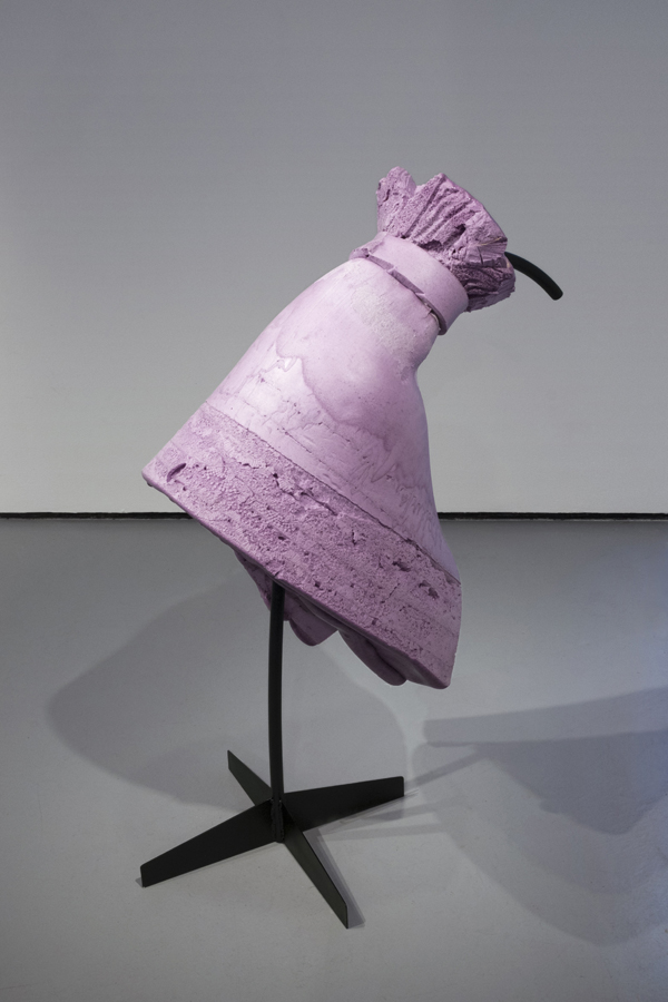 A closeup of a freestanding purple foam shape resembling a dress from the backside. The dress is supported by a tree-stand black metal frame.