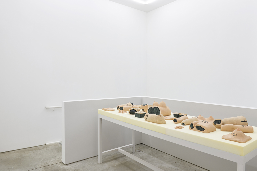 Installation view at the SculptureCenter. There is a long table covered in beige foam. Ontop lies various body parts made of painted ceramic. Arms, legs, torsos, chests, many of which also have tattoos carved into them in black. The walls of the room are bare white, except for two color drawings of some of the body parts on the table.