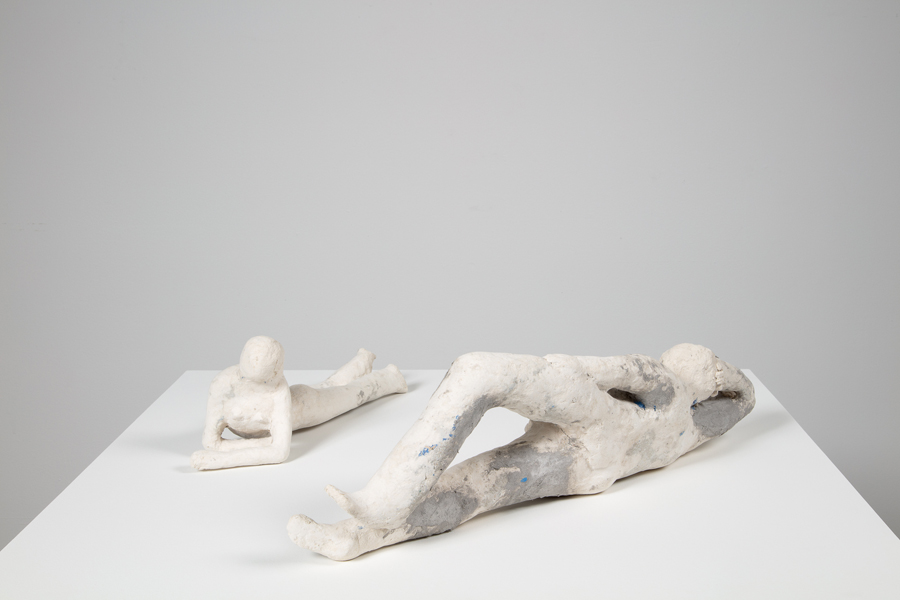 Two small white papier mache figures on a pedestal, facing each other. A female figure lies on her stomach while a male figure lies on his side.