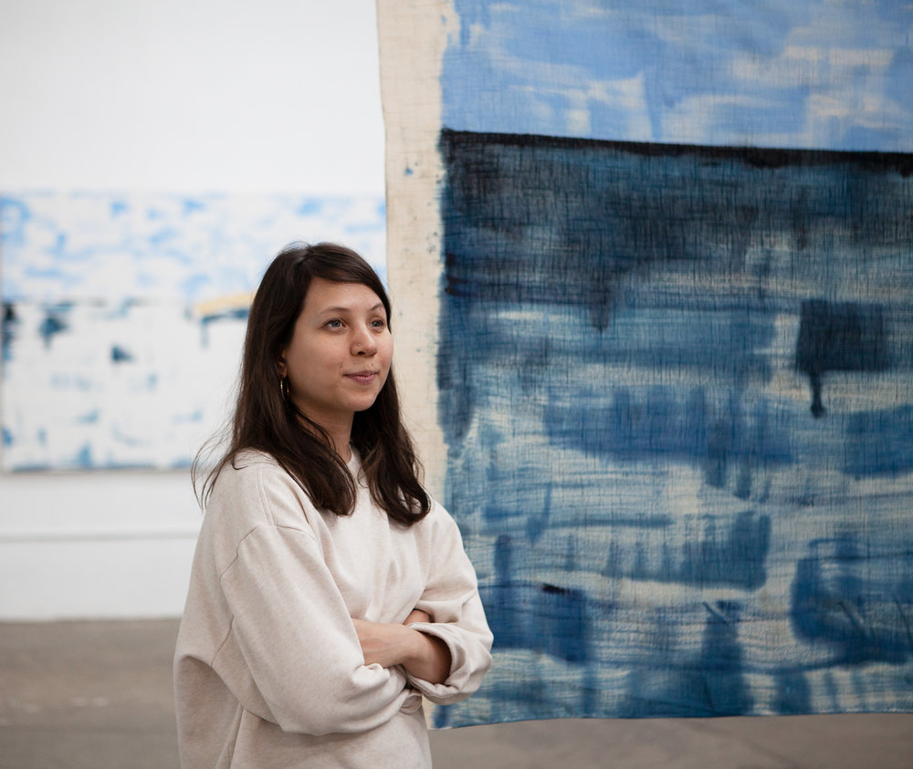 A portrait of Gossiaux standing in front of one of her paintings. She is wearing a beige sweater, crossing her arms, and striking a confident pose.