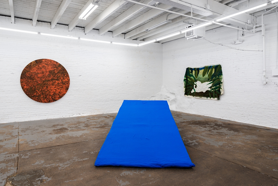 Installation view showing a large cerulean blue foam wedge in the foreground and a dark orange sun tapestry and a green painting on loose fabric hanging on the wall in the background.