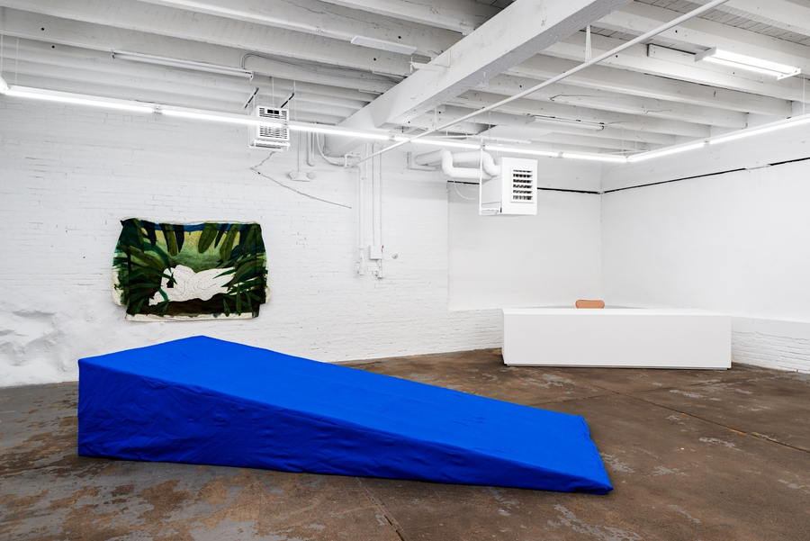 Installation view showing a large cerulean blue foam wedge in the foreground and a green painting on loose fabric hanging on the wall in the background.