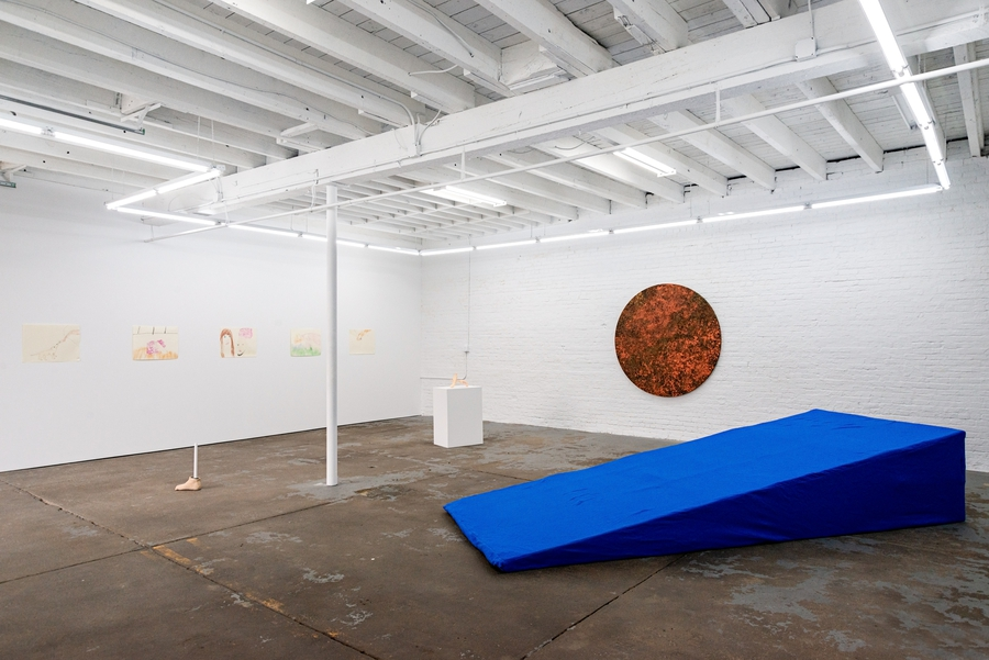 Installation view showing a large cerulean blue foam wedge in the foreground and a dark orange sun tapestry hanging on the wall in the background.
