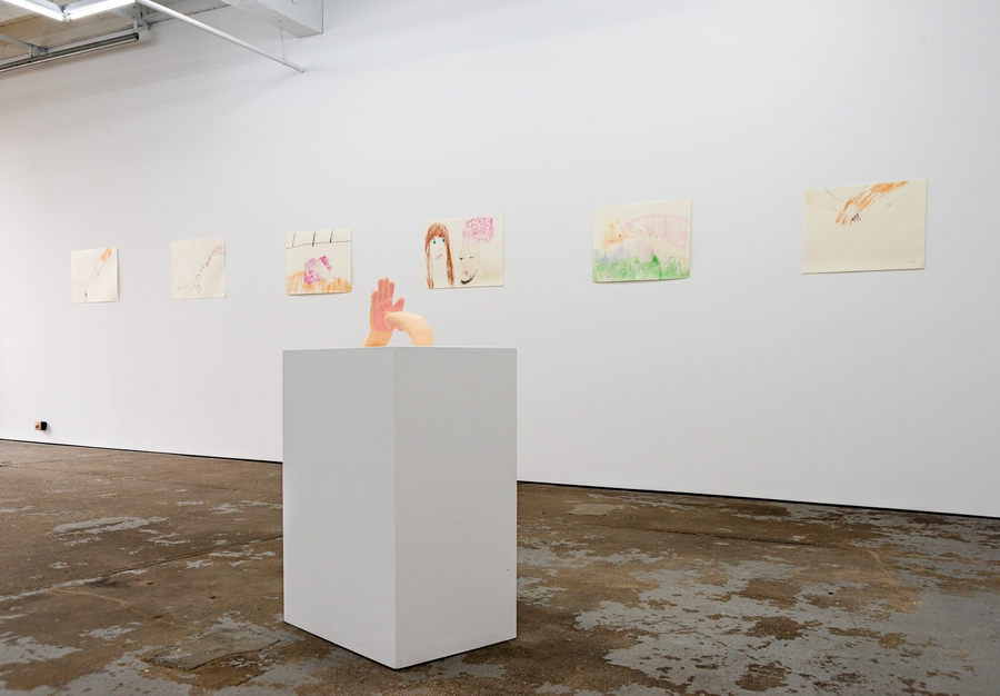 Installation view of a sculpture of two peach-colored hands on a white pedestal. One hand is pointing its index finger through the palm of the other hand. There are four pen and crayon drawings on the wall in the background.